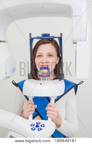A young dentist taking a panoramic digital X-ray of a patients teeth