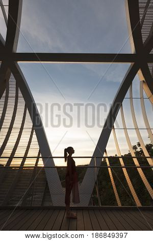 woman dancer isolated on a modern bridge with metal structure at dawn