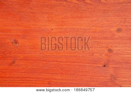 Painted red board with visible tree structure with large slats and knots