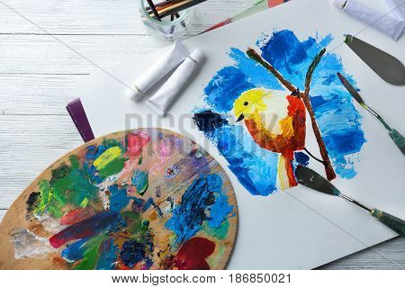 Colorful painting of bird on branch, palette and oil paints on table