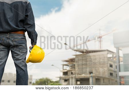 Engineer or safety officer holding yellow helmet with the building is background in construction site.