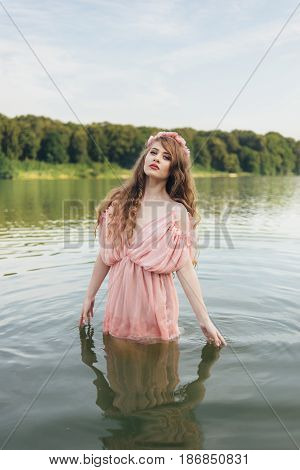 girl in a dress in the water at dawn