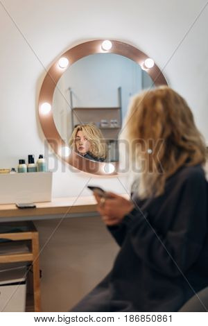 Attractive woman primp at the mirror with lamps in the beauty studio. A happy satisfied customer of make-up and hairstyle service.