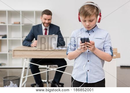 Business Attire Entrepreneur At Office With His Son Listening Music In Foreground