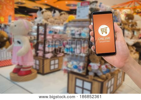 human hand hold smartphone tablet cell phone with online shopping application screen on blurry toy shop background. concept of online shopping.