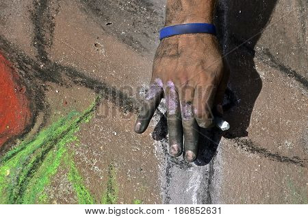 Dirty fingers and fingernails of an artist drawing on a sidewalk with colorful chalk.