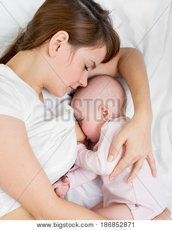 mother breast feeding and hugging her baby daughter