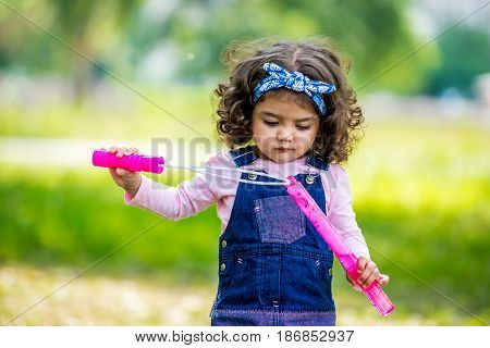 little girl blowing bubbles. Portrait of cute girl blowing soap bubbles. African-American girl blowing bubbles