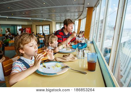 Two preschool kids and father boys eating pasta hamburger sitting in cafe on cruise ship. Happy children, twins and dad eating healthy organic and vegan food in restaurant. Childhood, health concept