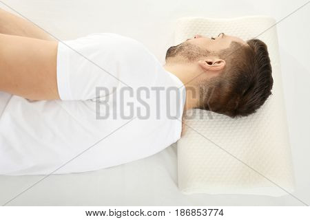 Young man lying on bed with orthopedic pillow. Healthy posture concept
