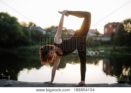 Pretty woman doing yoga exercises in the park on water background