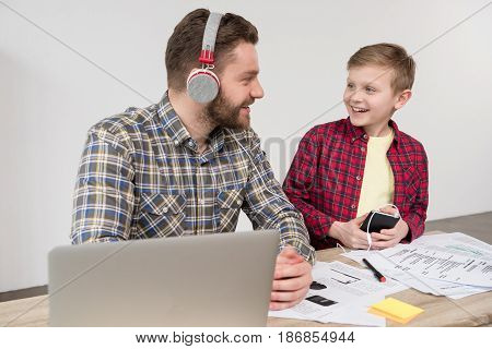 Businessman In Headphones With Son At Office