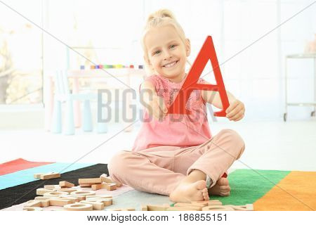 Cute little girl with letter A sitting on floor at home