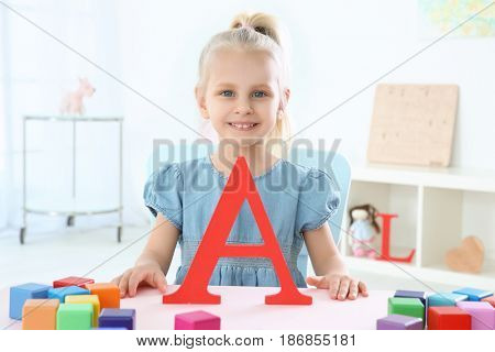 Cute little girl with letter A and colorful cubes at home