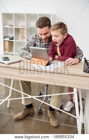 Businessman Using Tablet Computer With Son At Office