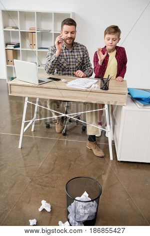 Businessman Freelancer Playing Trashketball With Son At Home Office