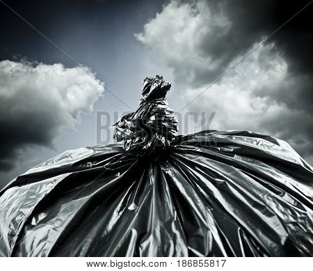 Black garbage bag and stormy sky outside. Apocalypse and pollution concept.