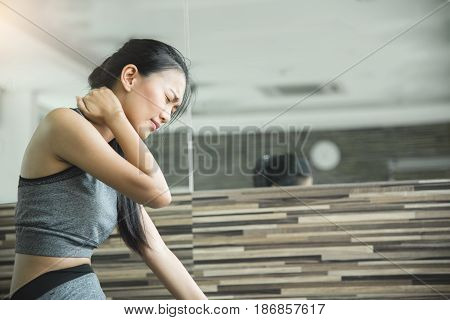 Asian woman having neck pain after workout at the gym.