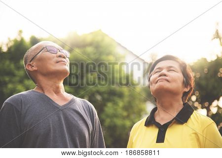 Happiness Couple Asian senior man and woman relaxing and breathing fresh air at park with sunlight. copy space. Plants Natural background.