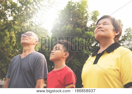 Happiness Group Asian family relaxing and breathing fresh air at park with sunlight. copy space. Plants Natural background.