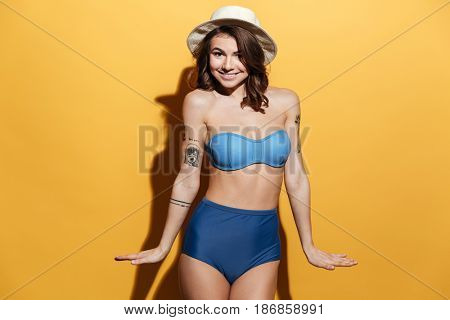 Image of smiling young woman in swimwear isolated over yellow background. Looking at camera.