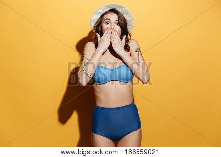 Picture of shocked young woman in swimwear isolated over yellow background. Looking at camera.