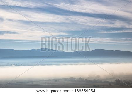 Beautiful morning atmosphere in a valley surrounded by hills with a magic mist full of bright light and white clouds and blue sunny sky