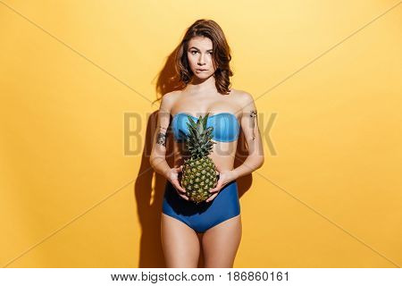Image of pretty young woman in swimwear isolated over yellow background holding pineapple. Looking at camera and bite lip.