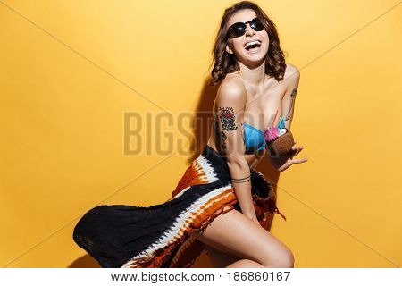 Image of cheerful young lady in swimwear isolated over yellow background holding cocktail.