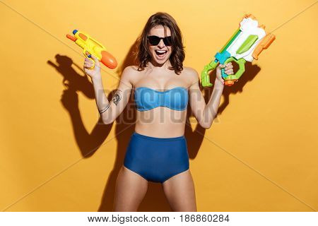Picture of screaming young woman in swimwear isolated over yellow background holding toys water gun. Looking at camera.