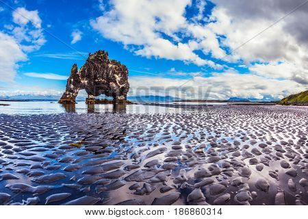Rock Hvitserkur on the sea beach in the form of a huge mammoth. The north coast of Iceland. Ocean tide at sunset. The concept of extreme northern tourism
