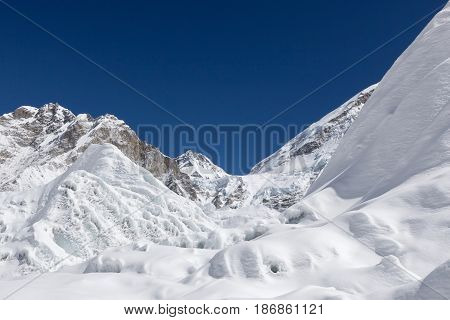 Beautiful Snowdrift And Ice Covered Mountains View Up To The Peaks And Blue Sky With White Clouds Fr
