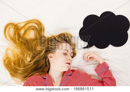 Teenage sleepwear fashion concept. Young woman lying on bed wearing cute pink pajamas black thinking or speech bubble next to her.