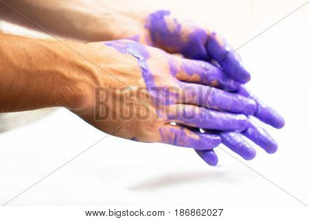 Man hands dirty by purple paint as decoration housework painter color bright light background concept