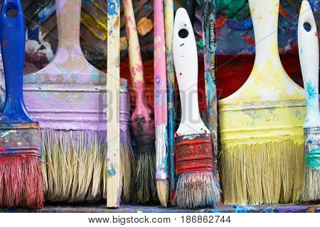 Old dirty messy artistic and craft work paintbrush set as colorful art homework innovative design concept and creativity paint palette background