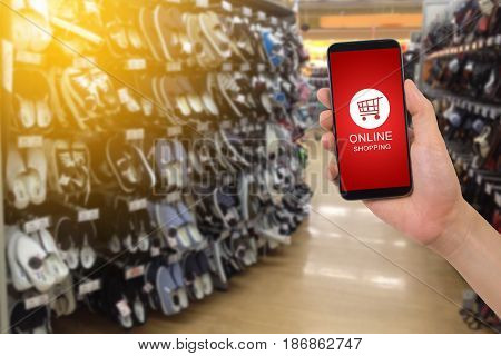 human hand hold smartphone tablet cell phone with shop cart online shopping on blurry footwear shop Online shopping concept.