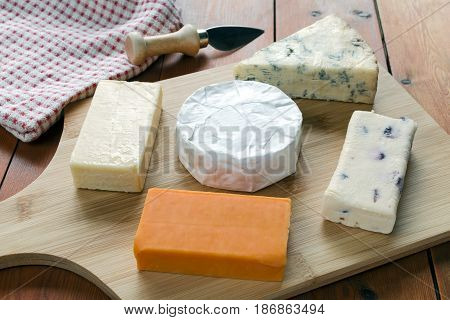 Cheese board selection on a wooden table with a red checked cloth and knife