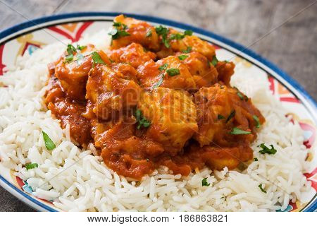 Chicken tikka masala with rice on wooden background