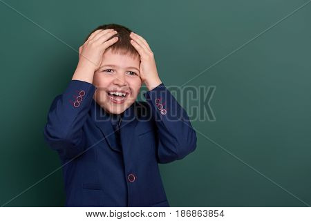 very emotional school boy portrait near green blank chalkboard background, dressed in classic black suit, one pupil, education concept