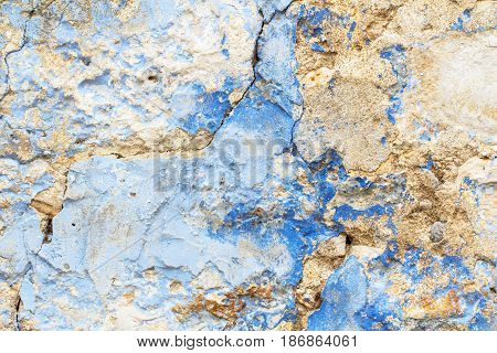 Old stone rustic cracked wall rough painted in blue paint as decay texture background