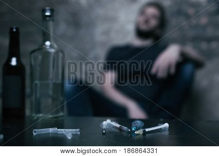 Blurred poisoned reality. Used medical unpacked syringes lying on the table while freak sitting in the background