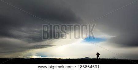 Silhouette of man watching big stormy clouds and the force of nature. Extreme weather in the Highland of Iceland with a blue eye of the storm.