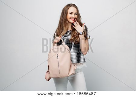 Beautiful and sexy brunette woman after beauty salon, sensuality posing, touching wavy hair by hand and smiling. Fashionable girl in striped blouse and white jeans posing holding beige leather bag.