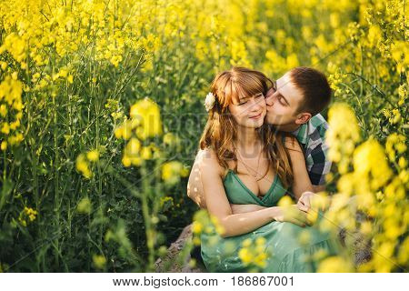 Young couple sitting among yellow flowers in meadow embrscing, man kissing his pretty wife. Girlfriend wearing green dress, husband in checked shirt. Walking outdoor in summertime