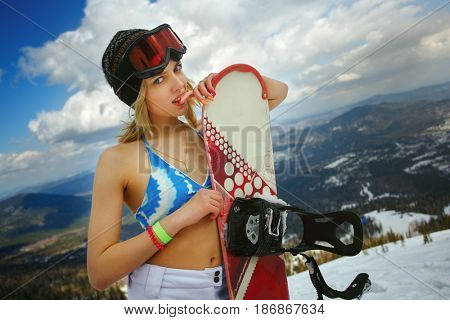 girl in a swimsuit with a snowboard on the ski slope