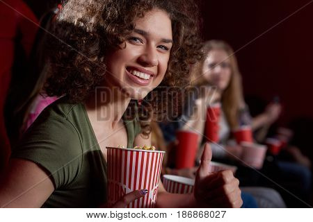 Side view of beautiful smiling woman with volumed curly hair looking, posing at camera at cinema hall, holding tasty popcorn. Young emotionally brunette girl watching funny movie at modern cinema.