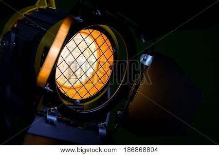 Fresnel lens, barn doors, protective metal mesh. Spotlight with directional light. Halogen lamps. Close-up.