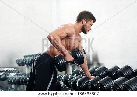 Shot of a muscular young man during weightlifting workout at the health club copyspace gym fitness ripped muscles strength sexy masculine sportsperson people lifestyle concept.