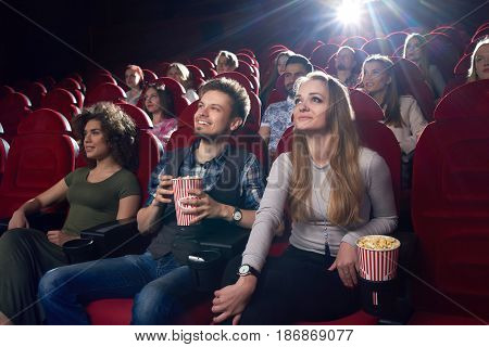 Smiling positive couple of boyfriend and blonde girlfriend watching funny movie at cinema . Best friends spending time together, eating popcorn when looking at project. Big fiends group.