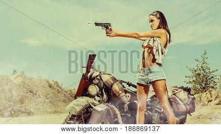Sexy Biker Woman With The Gun Near Motorbike On The Desert Background.
